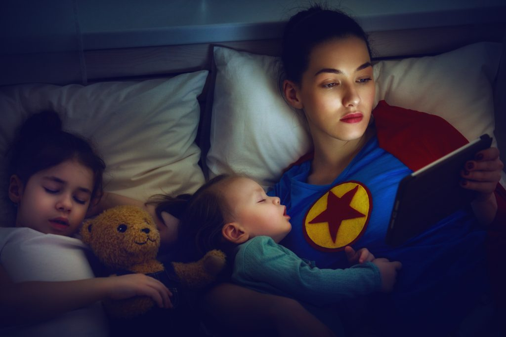 Adorable little children girls are napping in the bed with their mom. Quiet sleep with teddy bear under the protection of the mother superhero.